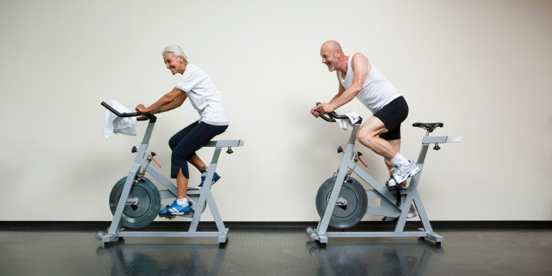 A senior woman and a mature man riding stationary bikes